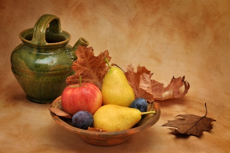 Old clay bowl full of autumn fruit photo
