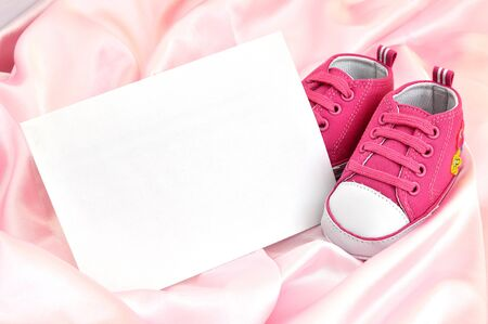 Pink baby booties and a blank card on pink silk photo