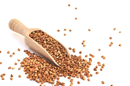 Buckwheat in a wooden scoop, isolated on white
