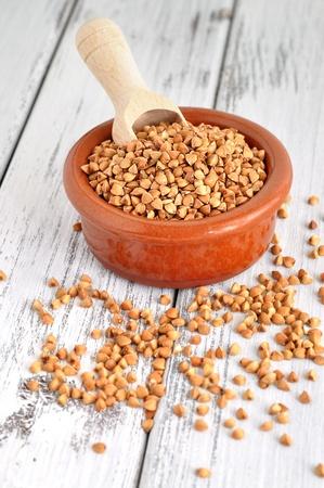 kasha: Buckwheat kasha and a wooden scoop in a clay bowl