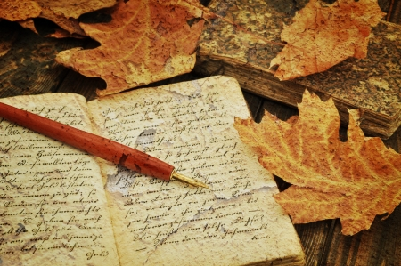 Fountain pen on old handwritten book with autumn leaves photo