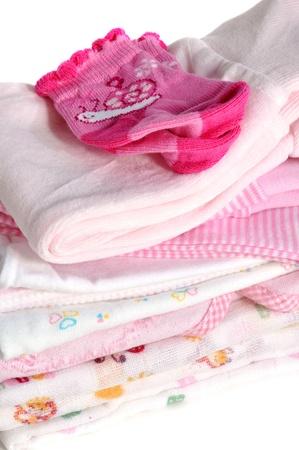 Chaussettes de bébé rose sur un tas de vêtements pour bébé Banque d'images
