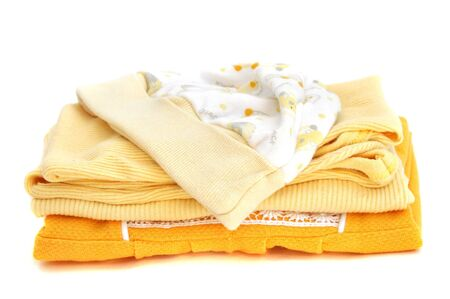 Pile of folded yellow baby clothes, isolated on white photo