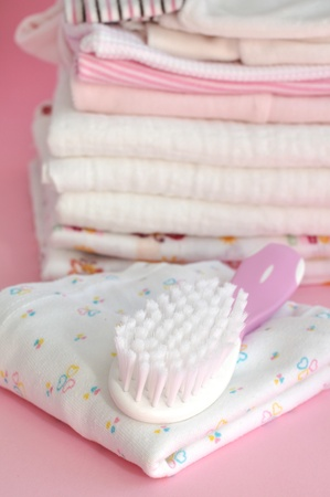Hairbrush and a pile of baby clothes and diapers on pink photo