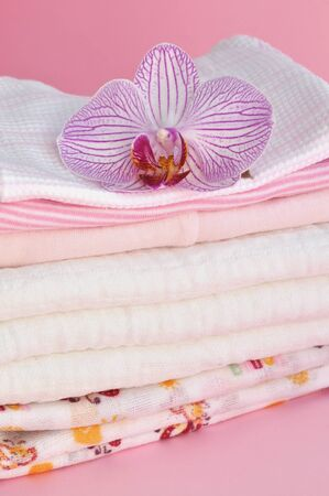 Pink orchid on a pile of baby clothes photo