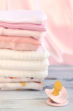 cotton dress: Pacifier and a pile of pink baby laundry and diapers on a wooden table
