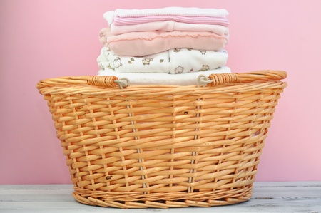 Laundry basket full of ironed pink baby clothes Stock Photo