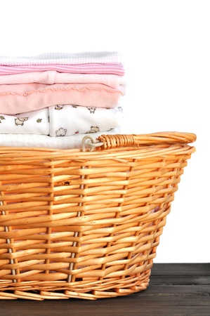 Laundry basket full of ironed pink baby clothes, isolated on white photo