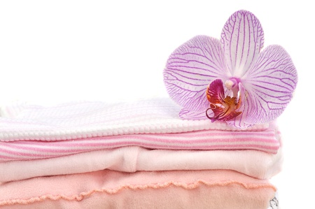 clean clothes: Orchid on a pile of folded pink laundry, isolated on white