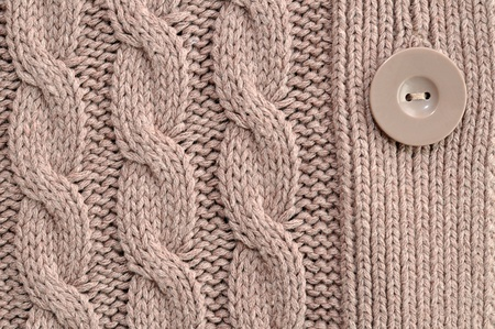 Brown knitted woolen background with button photo