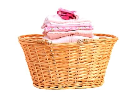 laundry: Ropa doblada rosa bebé en una cesta de mimbre, aislado en blanco Foto de archivo