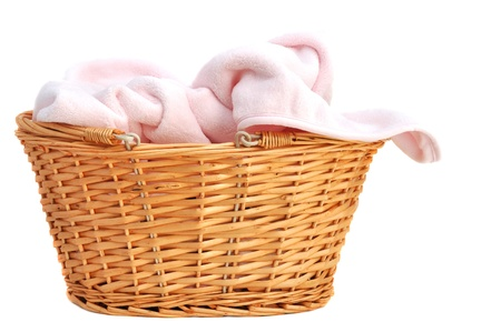 Soft pink baby blanket in a wicker basket, isolated on white photo