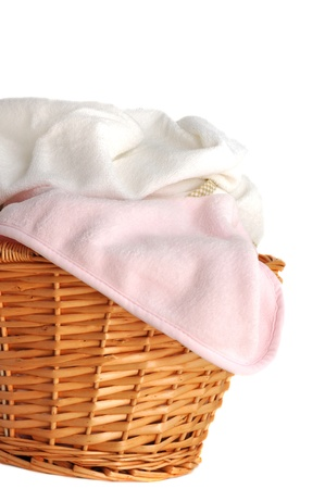 Soft pink baby blanket and white towel in a wicker basket, isolated on white photo