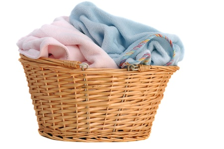 Soft pink and blue baby blanket in a wicker basket, isolated on white photo