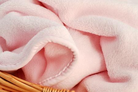 Soft pink baby blanket in a wicker basket in full frame