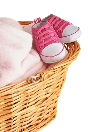 Soft pink baby blanket and booties in a wicker basket, isolated on white photo
