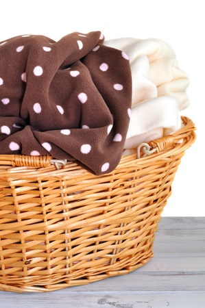 Soft fleece baby blankets in a wicker basket, isolated on white
