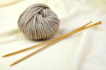 gomitoli di lana: Gomitolo di filato di cotone beige e ferri da calza Archivio Fotografico