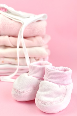 Booties, and a pile of pink baby laundry photo