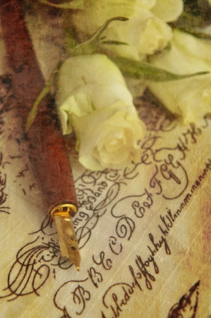 Fountain pen and white roses on handwritten words, toned sepia photo