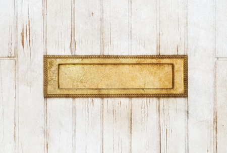 Old golden mailbox in the white wooden door photo