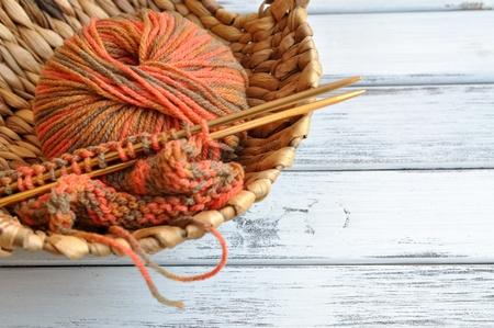 Agujas de tejer e hilos de colores del otoño en una cesta de mimbre