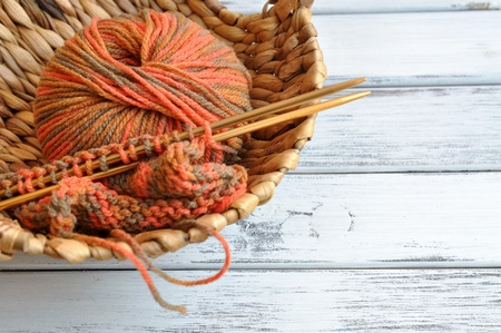 Knitting needles and yarn in autumn colors in a wicker basket photo