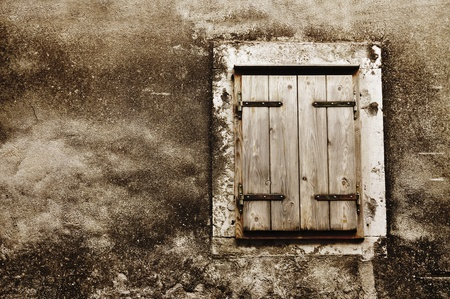 Old grunge window with closed shutters photo