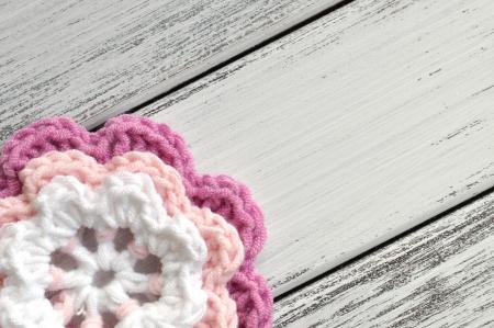 Crochet rosa y flor blanca sobre una mesa de madera Foto de archivo