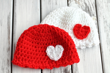 crochet: Two Valentines day crochet baby hats with hearts Stock Photo