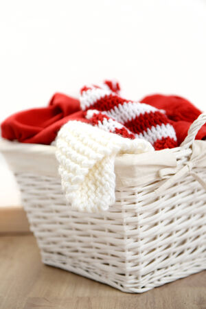 clean clothes: Red and white Christmas clothes in a wicker basket, isolated on white Stock Photo