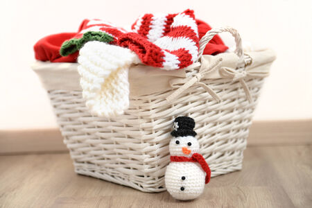 laundry basket: Red and white Christmas clothes in a wicker basket, isolated on white Stock Photo