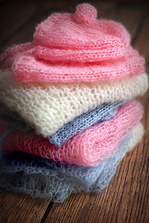 Pile of soft mohair hand knit clothes in pink, blue and white Stock Photo