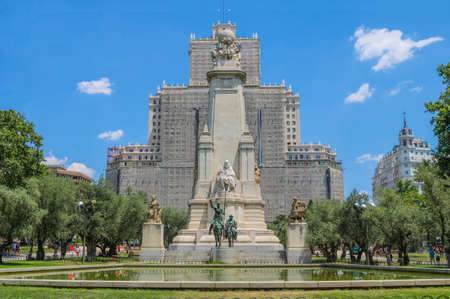 Monumento Cervantes upfront. Behind is the Edificio España under reparations. Shoot in July 2018. This picture was taken in Madrid, Spain. Reklamní fotografie