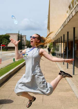 Blonde girl jumping, catching a water bottle Stok Fotoğraf