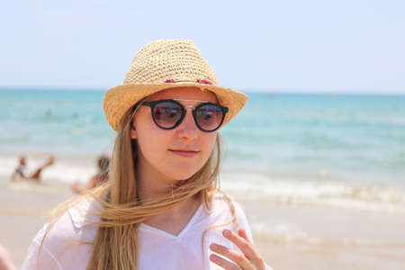 Blonde woman with hat and sunglasses on the sea