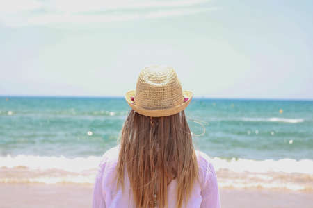Pretty blonde woman observing the sea