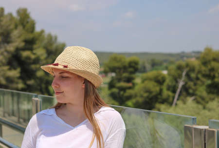 Blonde girl with a trilby hat posing on a glass bridge