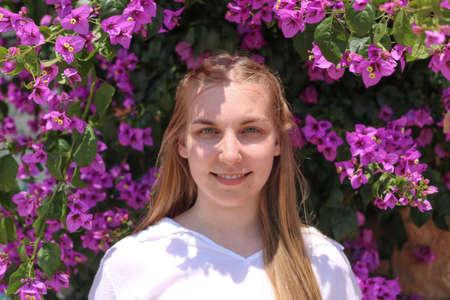 Blonde girl posing behind bougainvillea