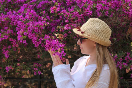 Blonde girl posing and smelling bougainvillea