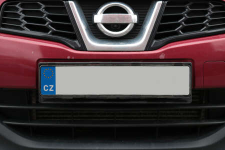 Empty License plate in the front of a red car