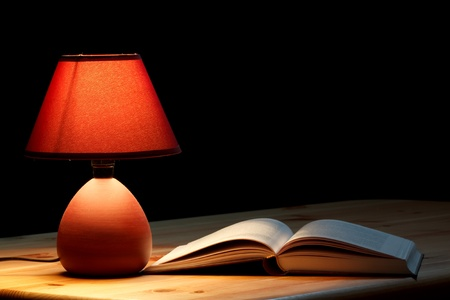 night table: Lamp illuminating a book on wooden table