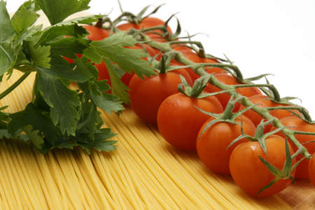 Chery tomato and parsly with uncooked pasta Stock Photo