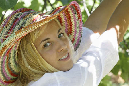 Girl wearing a colorfull hat posing under a tree