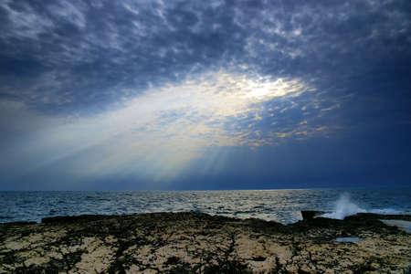 Sunrays shooting trough a cloud on a beach.