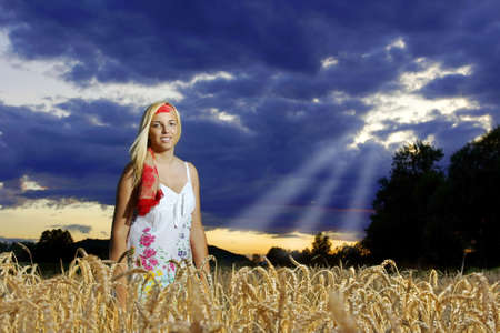 Girl standing in a wheat field against a cloudy sky.