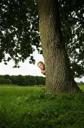Girl hideing behind a tree.