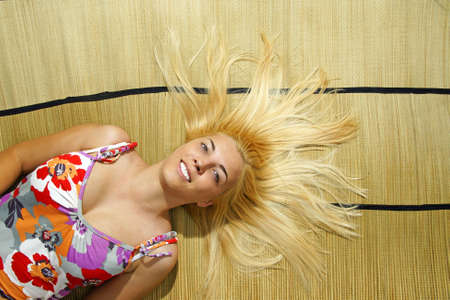 Girl lying on a bamboo mat.