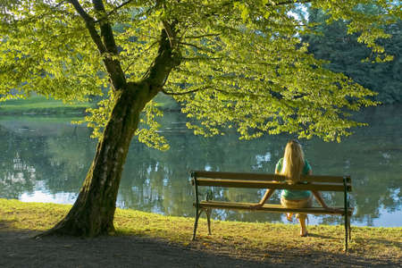 Girl sitting under a tree by the river.