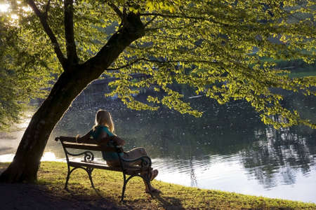 Girl siting on a bench under a tree by the river.